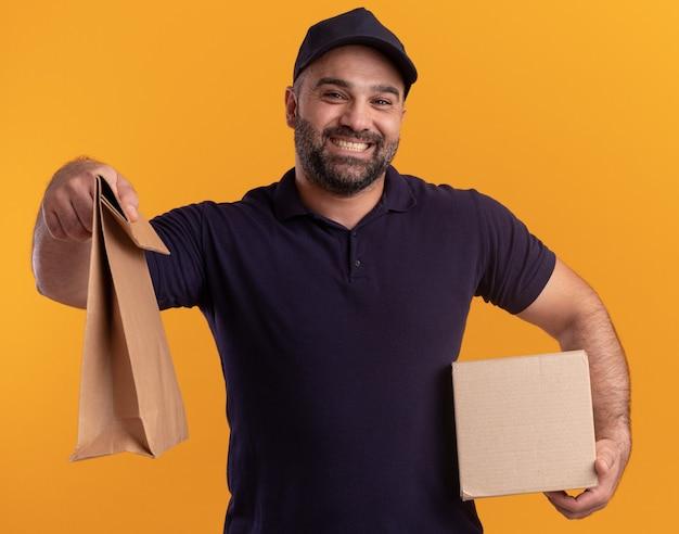 Entregador de meia-idade sorridente de uniforme e boné segurando uma caixa e segurando um pacote de comida de papel isolado na parede amarela