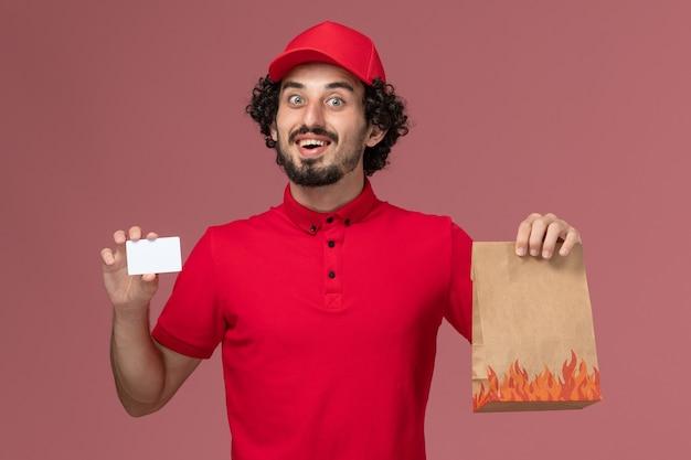 Entregador de mensageiro masculino de camisa vermelha e capa de frente segurando um pacote de comida e cartão na parede rosa.