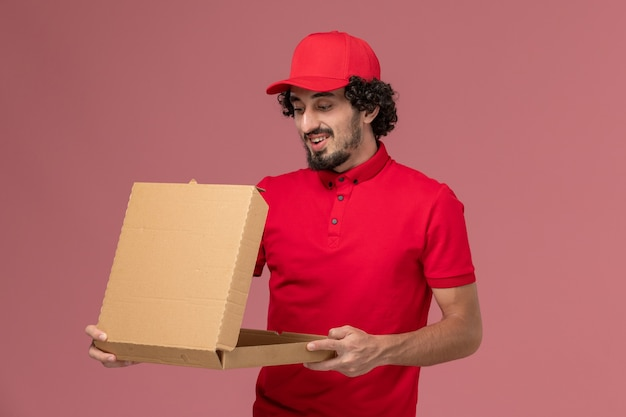 Entregador de mensageiro masculino de camisa vermelha e capa de frente segurando uma caixa de comida na parede rosa funcionário da empresa de entrega de serviços