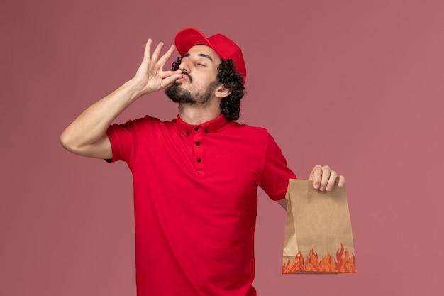Entregador de mensageiro masculino de camisa vermelha e capa segurando um pacote de comida na parede rosa.