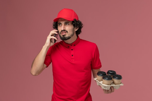 Entregador de mensageiro masculino de camisa vermelha e capa segurando xícaras de café de vista frontal, falando ao telefone na parede rosa.
