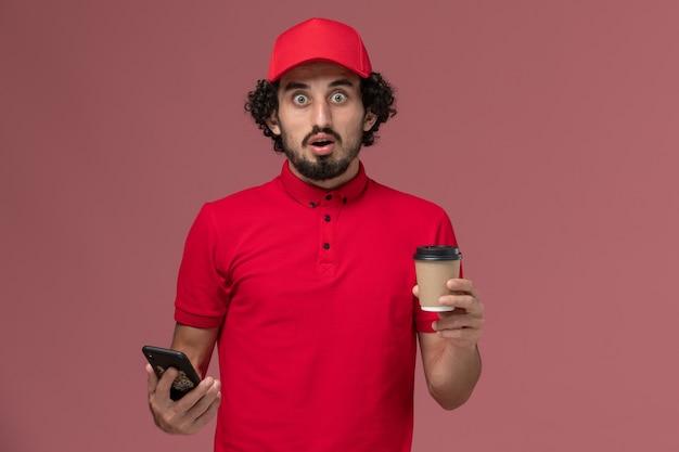 Entregador de mensageiro masculino de camisa vermelha e capa, vista frontal, segurando a xícara de café marrom e usando seu telefone na parede rosa claro.