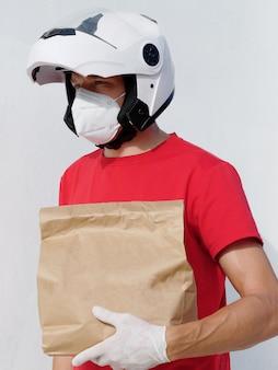 Entregador de motociclista de uniforme. segura um saco de papelão com luvas de proteção médica e máscara kn95. compras on-line e entrega expressa.