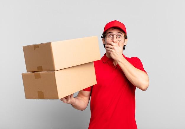 Entregador de pacotes cobrindo a boca com as mãos com uma expressão chocada e surpresa, mantendo um segredo ou dizendo oops
