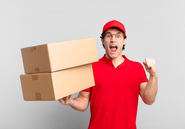 Entregador de pacotes gritando agressivamente com uma expressão de raiva ou com os punhos cerrados celebrando o sucesso