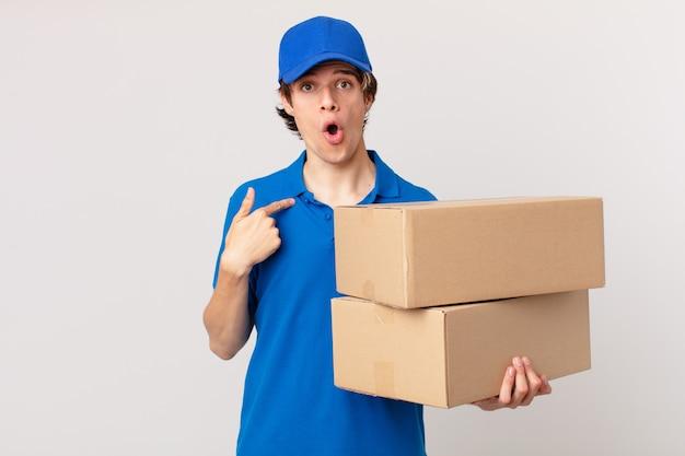 Entregador de pacotes parecendo chocado e surpreso com a boca aberta, apontando para si mesmo