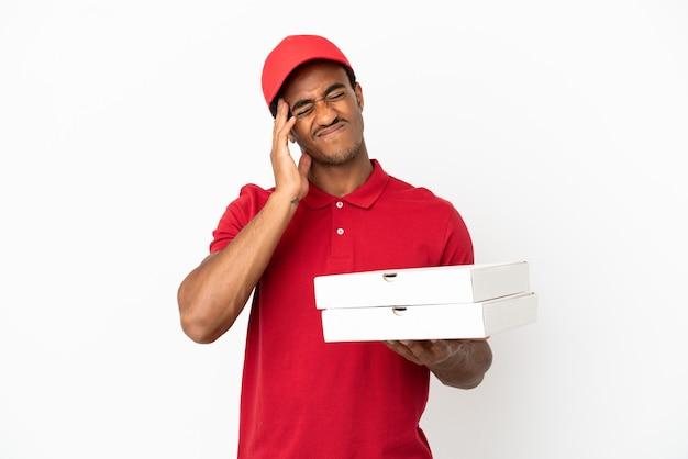 Entregador de pizza afro-americano pegando caixas de pizza em uma parede branca isolada com dor de cabeça