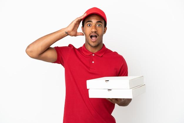 Entregador de pizza afro-americano pegando caixas de pizza em uma parede branca isolada com expressão de surpresa