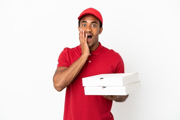 Entregador de pizza afro-americano pegando caixas de pizza em uma parede branca isolada com expressão facial de surpresa e choque