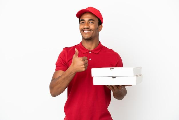Entregador de pizza afro-americano pegando caixas de pizza em uma parede branca isolada e fazendo um gesto de polegar para cima