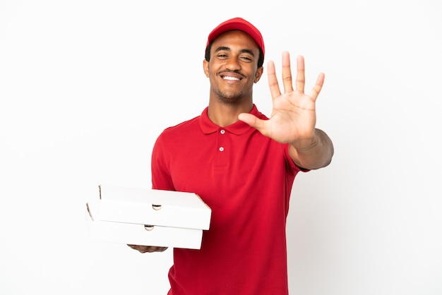 Entregador de pizza afro-americano pegando caixas de pizza na parede branca isolada e contando cinco com os dedos