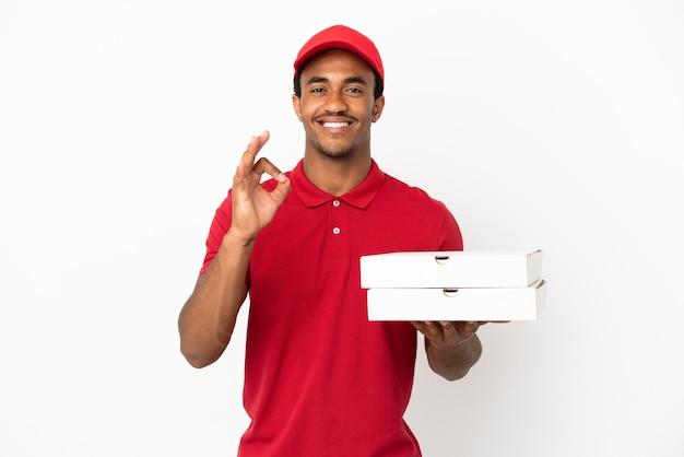 Entregador de pizza afro-americano pegando caixas de pizza na parede branca isolada, mostrando o sinal de ok com os dedos