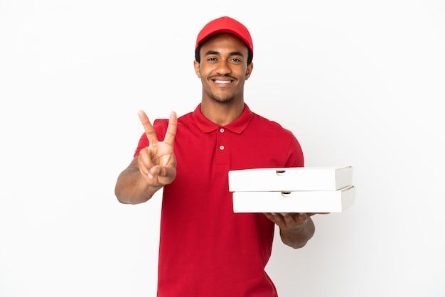 Entregador de pizza afro-americano pegando caixas de pizza na parede branca isolada, sorrindo e mostrando o sinal da vitória