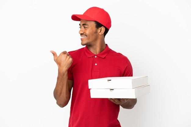 Entregador de pizza afro-americano pegando caixas de pizza sobre uma parede branca isolada apontando para o lado para apresentar um produto