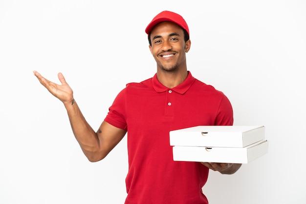 Entregador de pizza afro-americano pegando caixas de pizza sobre uma parede branca isolada e estendendo as mãos para o lado para convidar para vir