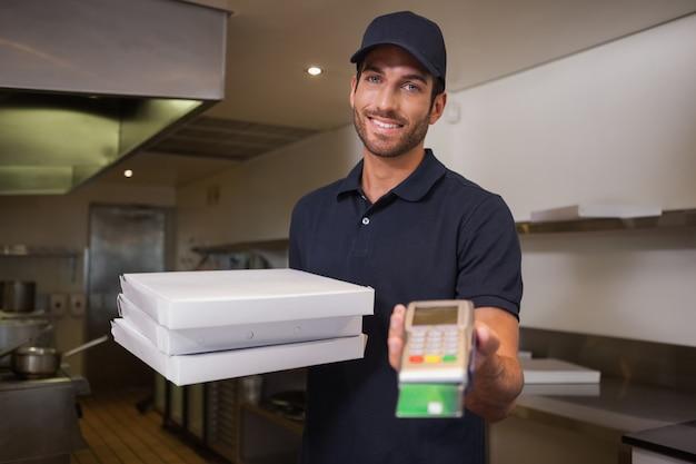 Entregador de pizza alegre segurando a máquina de cartão de crédito