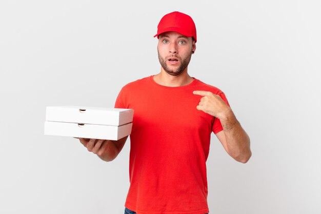 Entregador de pizza chocado e surpreso com a boca aberta, apontando para si mesmo