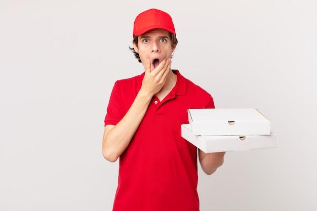 Entregador de pizza com boca e olhos bem abertos e mão no queixo