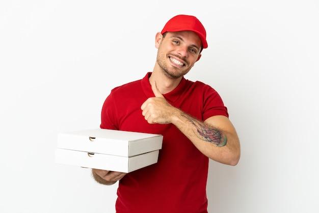 Entregador de pizza com uniforme de trabalho pegando caixas de pizza em uma parede branca isolada e fazendo um gesto de polegar para cima