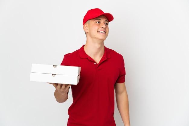 Entregador de pizza com uniforme de trabalho pegando caixas de pizza isoladas na parede branca pensando uma ideia enquanto olha para cima