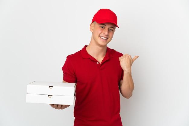 Entregador de pizza com uniforme de trabalho pegando caixas de pizza isoladas no fundo branco apontando para o lado para apresentar um produto