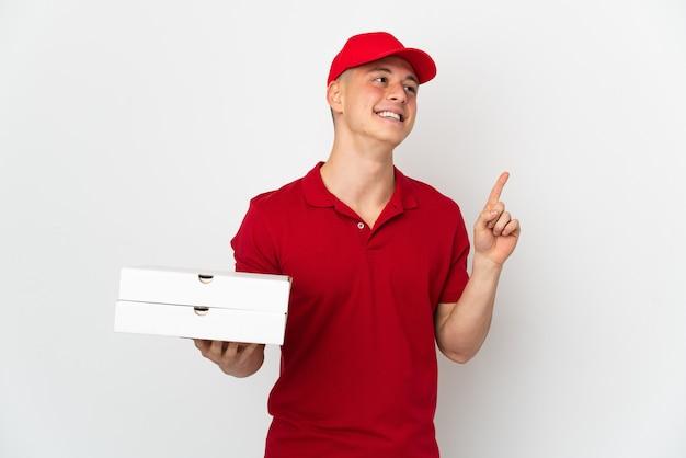 Entregador de pizza com uniforme de trabalho pegando caixas de pizza isoladas no fundo branco apontando uma ótima ideia