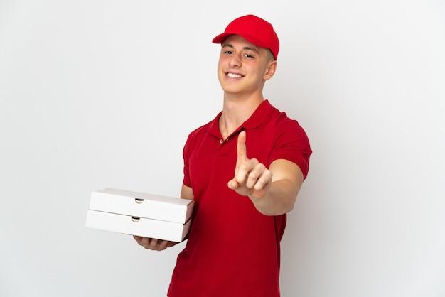 Entregador de pizza com uniforme de trabalho pegando caixas de pizza isoladas no fundo branco, mostrando e levantando um dedo