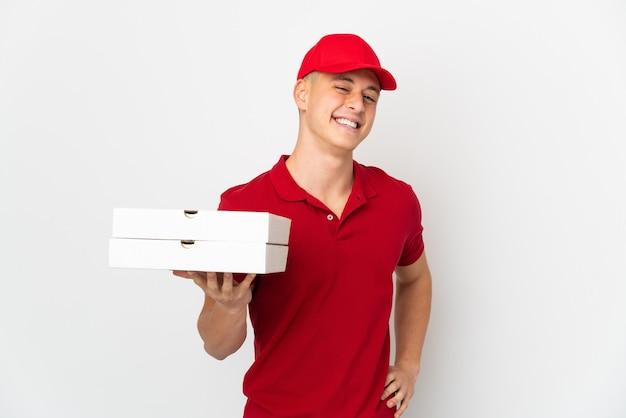 Entregador de pizza com uniforme de trabalho pegando caixas de pizza isoladas no fundo branco, posando com os braços na cintura e sorrindo