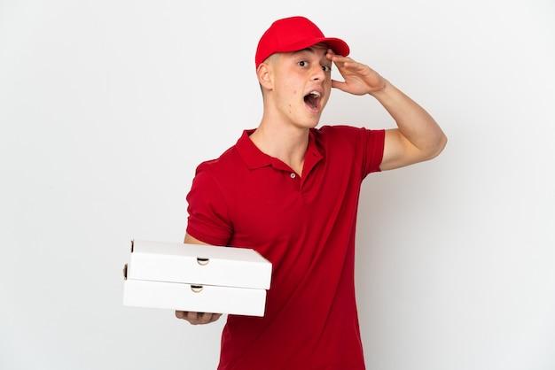 Entregador de pizza com uniforme de trabalho pegando caixas de pizza isoladas