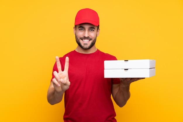 Entregador de pizza com uniforme de trabalho, pegando caixas de pizza sobre parede amarela isolada, sorrindo e mostrando sinal de vitória