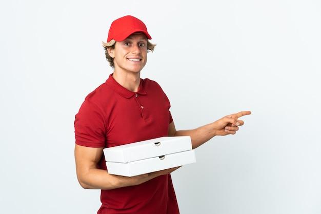 Entregador de pizza em uma parede branca isolada apontando o dedo para o lado