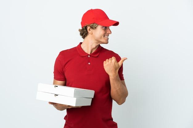 Entregador de pizza em uma parede branca isolada apontando para o lado para apresentar um produto
