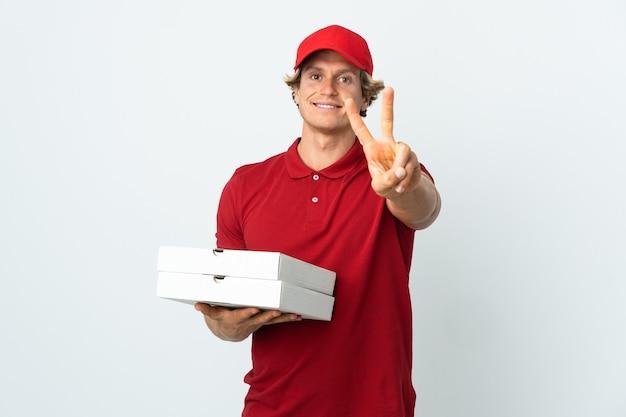 Entregador de pizza em uma parede branca isolada sorrindo e mostrando sinal de vitória