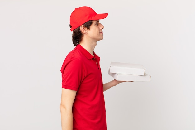 Entregador de pizza em vista de perfil pensando, imaginando ou sonhando acordado