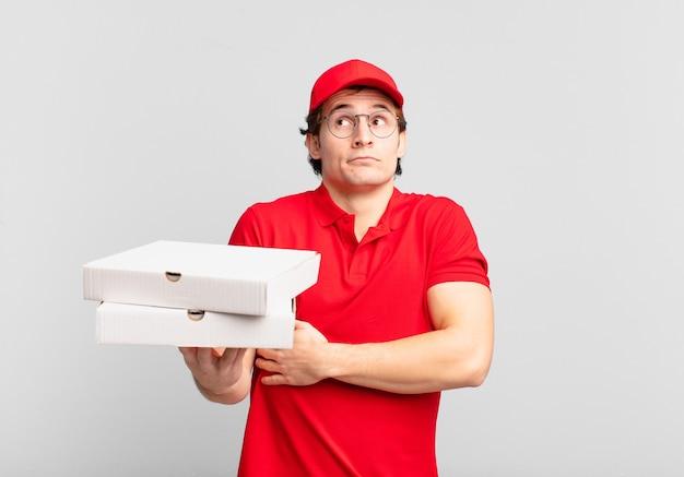 Entregador de pizza encolhendo os ombros, sentindo-se confuso e incerto, duvidando com os braços cruzados e olhar perplexo