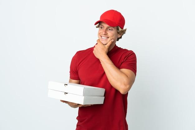 Entregador de pizza isolado olhando para o lado e sorrindo
