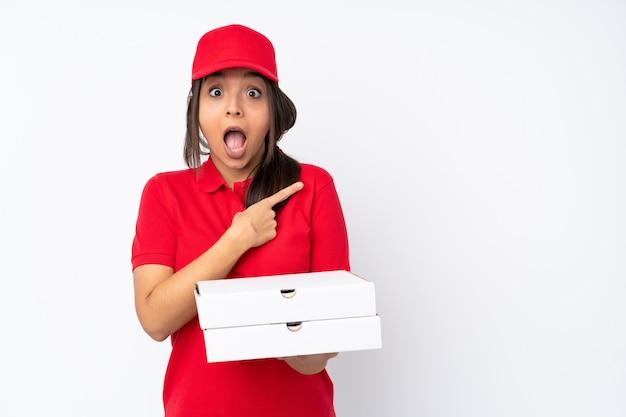 Entregador de pizza jovem sobre parede branca isolada surpreendeu e apontando o lado