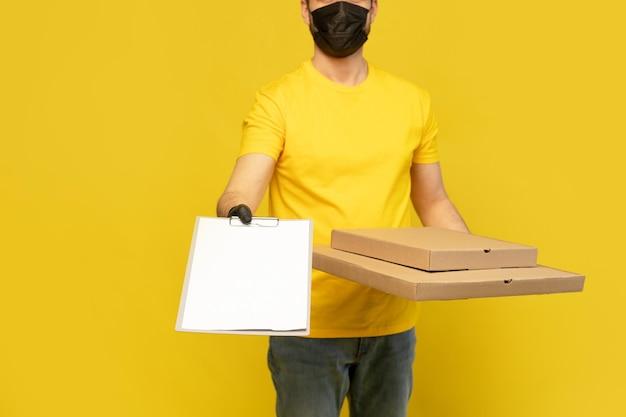 Entregador de pizza na máscara, olhando para a câmera isolada. conceito do coronavirus 2019ncov