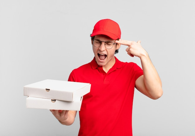 Entregador de pizza parecendo infeliz e estressado, gesto suicida fazendo sinal de arma com a mão, apontando para a cabeça