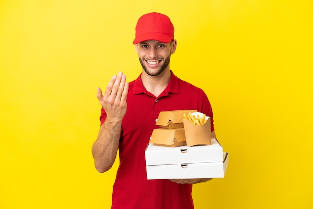 Entregador de pizza pegando caixas de pizza e hambúrgueres sobre fundo isolado, convidando para vir com a mão. feliz que você veio