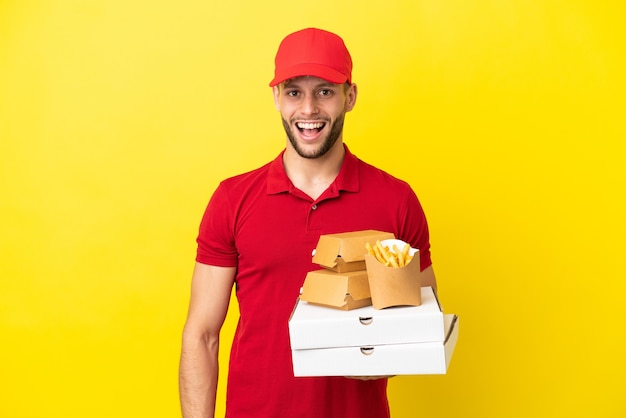 Entregador de pizza pegando caixas de pizza e hambúrgueres sobre um fundo isolado com expressão facial de surpresa