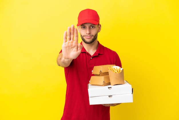 Entregador de pizza pegando caixas de pizza e hambúrgueres sobre um fundo isolado fazendo gesto de pare