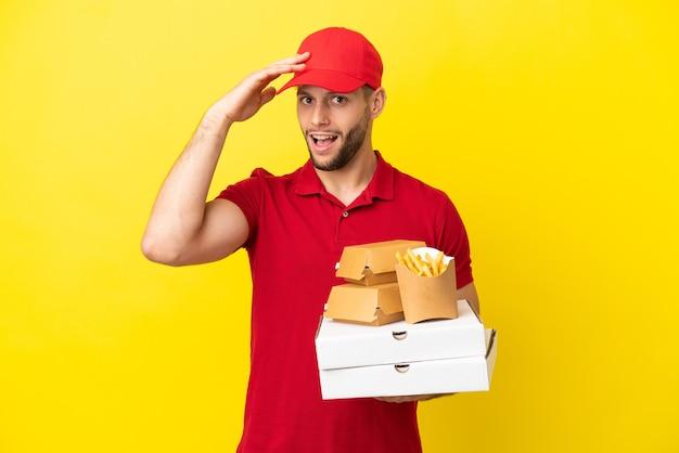 Entregador de pizza pegando caixas de pizza e hambúrgueres sobre um fundo isolado fazendo gesto de surpresa enquanto olha para o lado