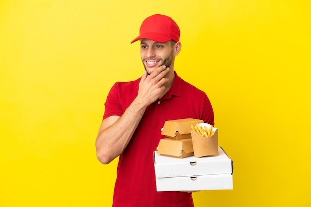 Entregador de pizza pegando caixas de pizza e hambúrgueres sobre um fundo isolado, olhando para o lado e sorrindo