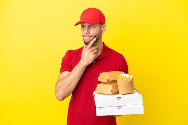 Entregador de pizza pegando caixas de pizza e hambúrgueres sobre um fundo isolado, tendo dúvidas e pensando