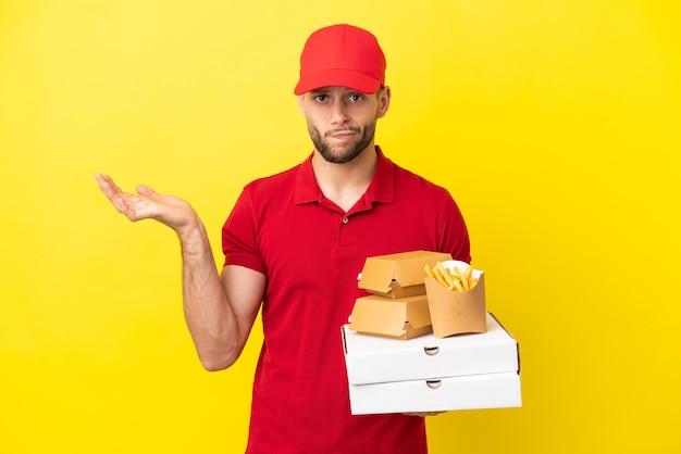 Entregador de pizza pegando caixas de pizza e hambúrgueres sobre um fundo isolado, tendo dúvidas enquanto levanta as mãos