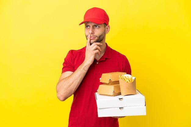 Entregador de pizza pegando caixas de pizza e hambúrgueres sobre um fundo isolado, tendo dúvidas enquanto olha para cima