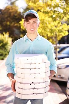 Entregador de pizza segurando caixas com pizza, ao ar livre