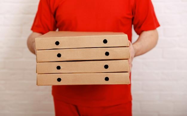 Entregador de pizza segurando caixas de entrega de pizza mais rápida da cidade