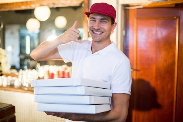 Entregador de pizza, segurando caixas de pizza, fazendo um gesto de telefone
